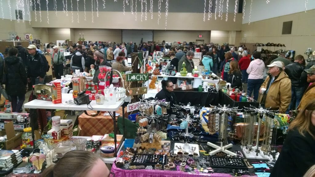 antiques on tables with shoppers at Jackson Flea Market
